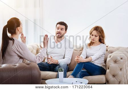 Stop fighting. Confident professional female psychologist holding her hands in front of her and looking at her patients while telling them to stop fighting