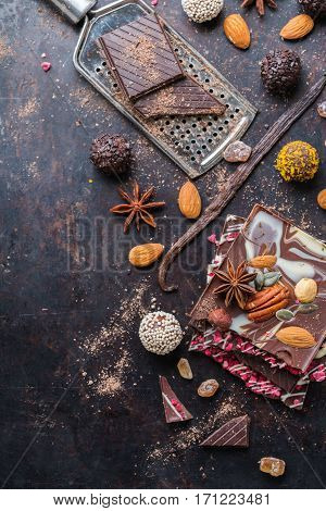 Sweet and treat, junk unhealthy food. Assortment of chocolate bar and praline with spices and nuts on black moody grunge table. Top view flat lay overhead
