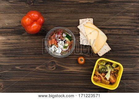 Eat your dinner. Yellow plastic box holding stewed vegetables standing near cheese with bread, little cherry tomato lying between two boxes
