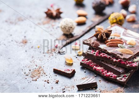 Sweet and treat, junk unhealthy food. Assortment of chocolate bar and praline truffle with spices and nuts on black moody grunge table. Copy space background