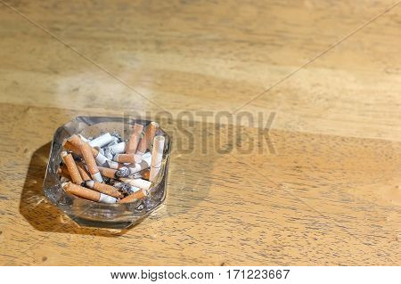Cigarette butts in the ashtray on wooden table