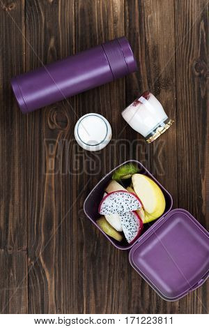 Enjoy the moment. Violet lunch box containing mix of kiwi and dragon fruit standing near two jars of yoghurt