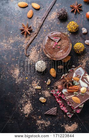 Sweet and treat, junk unhealthy food. Assortment of chocolate bar and praline truffle and mousse with spices and nuts on black moody grunge table. Copy space background, flat lay top view overhead