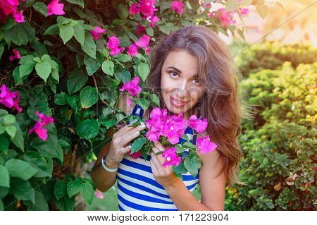 beautiful young woman on vacation near the flowering bougainvillea bush