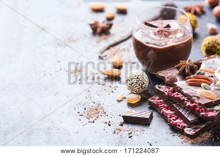 Sweet and treat, junk unhealthy food. Assortment of chocolate bar and praline truffle and mousse with spices and nuts on moody grunge table. Copy space background