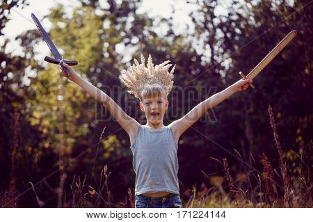 Portrait Boy with a crown on the head and a sword in hands in sunny summer day. Succes concept.