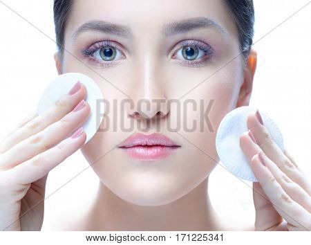 portrait of attractive young caucasian woman brunette isolated on white studio shot  face skin looking at camera hand care cleaning cotton discs makeup nails lips looking at camera beauty spa