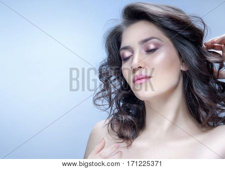 beauty portrait of attractive caucasian young woman brunette on blue background studio shot face skin hand makeup eyes closed lips hair neck