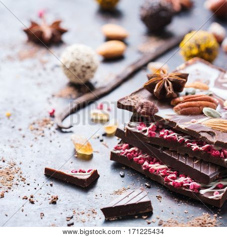 Sweet and treat, junk unhealthy food. Assortment of chocolate bar and praline truffle with spices and nuts on black moody grunge table