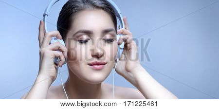 beauty closeup portrait of attractive young caucasian smiling woman brunette on blue background studio shot lips face head and shoulders eyes closed listening music headphones