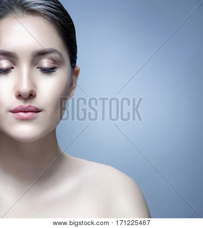 closeup portrait of attractive young caucasian woman brunette  on blue background studio shot lips face  head and shoulders skin care eyes closed