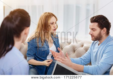 Family quarrel. Angry furious young woman looking at her husband and shouting while having a quarrel with him