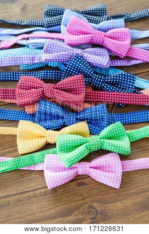 Variety of colorful bow ties on rustic wooden background