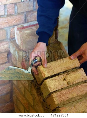 Trainee bricklayer positioning brick on wall support