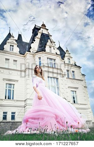 Wedding day. Gorgeous bride looking to the sky next to castle in east Slovakia
