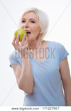 It is my diet. Amazing aged woman looking at camera keeping her mouth opened while going to bite a piece of apple, isolated on white background