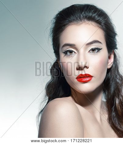 portrait of young beautiful woman with elegant makeup posing in photostudio