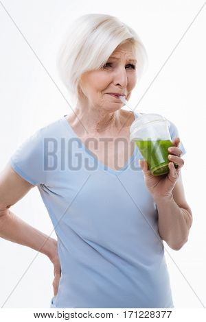 Bitter juice. Dissatisfied aged woman holding her right hand on the waist while drinking smoothie, isolated on white