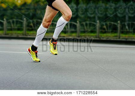 legs runner athlete running in compression socks on city street