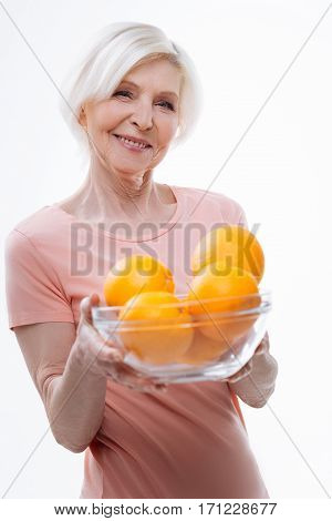 Orange mood. Delighted woman looking straight at camera keeping smile on the face while keeping oranges, standing in semi position over white background