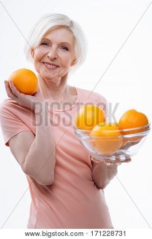 Make fresh juice. Good looking pretty female wearing pink tee shirt holding big nesting bowl with appetizing oranges posing over white background