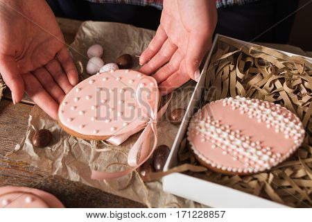 Woman packing handmade Easter cookies closeup. Top view on female hands holding sweet egg form pastry with pink glaze and gift box. Tradition, surprise, dessert concept