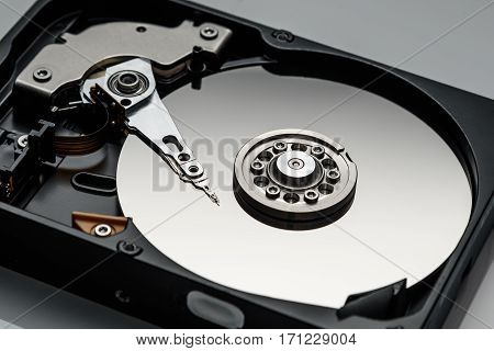 disassembled computer hard drive in silver color closeup isolated