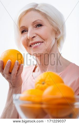 Feeling happiness. Attractive female keeping smile on her face holding bowl with oranges looking at camera, isolated on white background