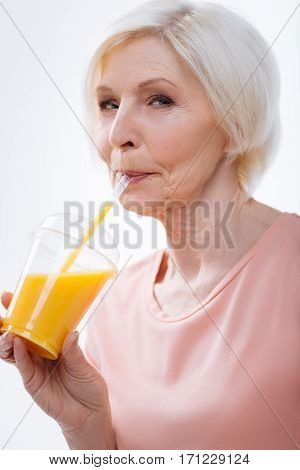 Keep fit. Delighted aged female wearing pink tee shirt holding glass of juice in right hand while looking at camera, isolated on white background