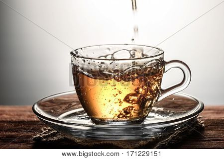 tea pouring into glass transparent Cup with bubbles on the wooden table