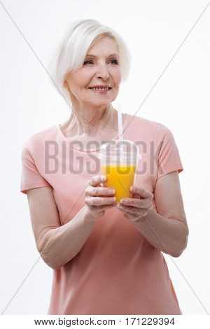 In good spirits. Beautiful aged female feeling courage holding full glass of fresh orange juice, standing over white background