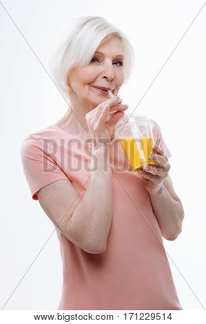 Be healthy. Attractive pensioner blonde woman keeping smile on her face holding full glass of fresh orange juice near her mouth, posing over white background