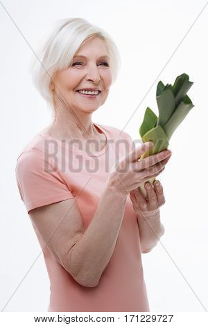 Green plant. Kind attractive smiling woman feeling happiness holding big green leek, standing over white background