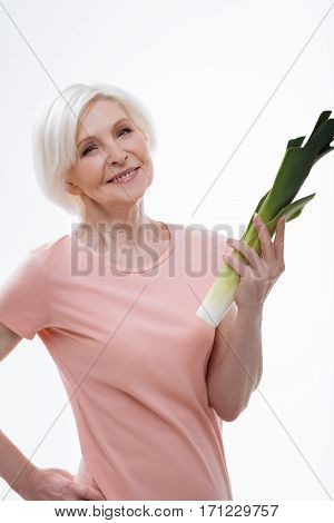 Healthy eating. Delighted female feeling courage holding her right hand on the waist while demonstrating leek, isolated on white background