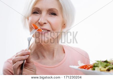 My dinner. Positive delighted woman keeping fork with tomato in right hand while going to eat it and holding plate with salad in left hand, isolated on white background
