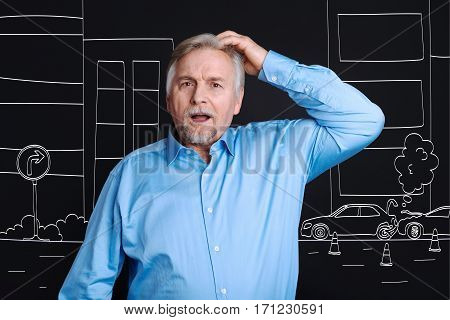 Heavy traffic. Emotional pleasant elderly man standing on the street and looking at the traffic jam while putting his hand to the head