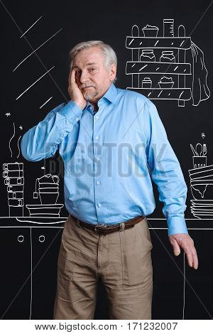 What a mess. Depressed unhappy senior man standing in the kitchen and putting his hand to the cheek while having lots of dirty dishes there