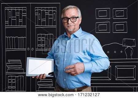 Successful businessman. Confident intelligent elderly man holding a tablet and smiling while standing in his office
