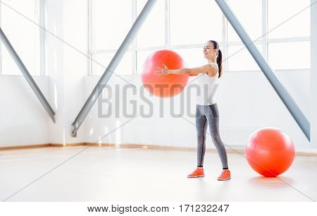 Special fitness equipment. Cheerful well built young woman holding a fitness ball and smiling while using it in her training