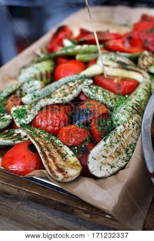 Vegan bbq party. Barbecue eggplants and tomatoes closeup. Cookout vegetable food. Fresh organic, healthy vegetarian snack, aubergines roasted on grill. Street fast food. Tasty natural meals