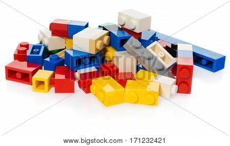 Stack of different colored blocks for children. Toy bricks in the colors: yellow red blue gray black on white background with slight reflection.