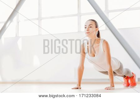 In the gym. Beautiful concentrated pleasant woman doing push ups and concentrating on the exercise while having a workout in the gym