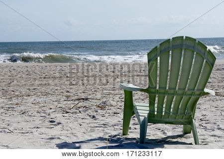 Green Adirondack Chair on the Beach with a View of the Ocean