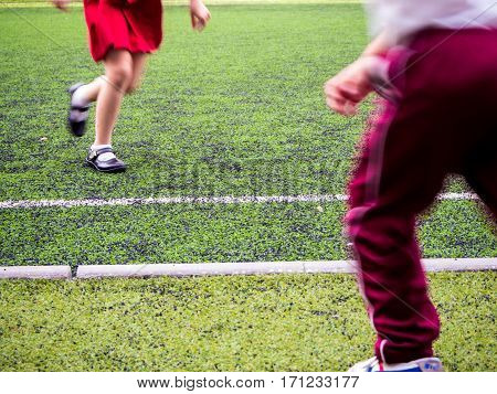 Children play on the artificial turf of the school