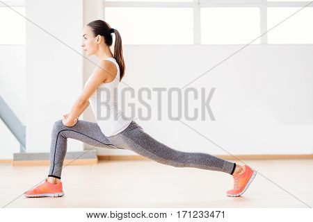 Active lifestyle. Nice confident beautiful woman standing in the gym and doing a physical exercise while having aerobics classes