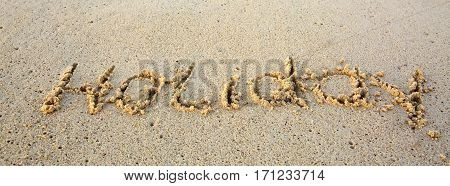 Holiday Written in sand at the beach. Holiday concept.