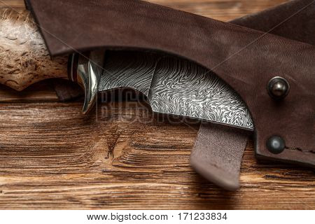Hunting damascus steel knife handmade in sheath on a brown wooden background, closeup
