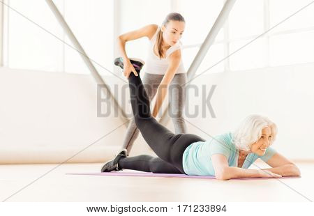 At the fitness centre. Skillful experienced female coach standing near the woman and holding her leg while looking at her
