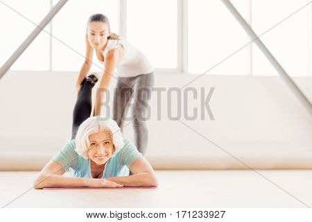 Pleasant workout. Joyful nice elderly woman lying on the floor and smiling while looking at you