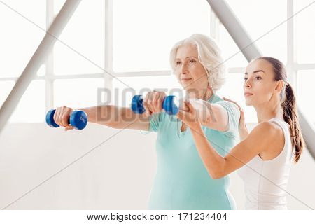 Building up muscles. Nice concentrated senior woman standing and holding dumbbells while working out in the fitness center